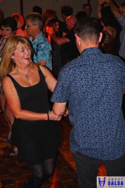 2 people dancing to salsa music. One in a black dress