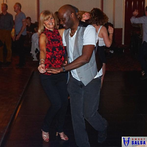 Two people salsa dancing. Lady in a red top