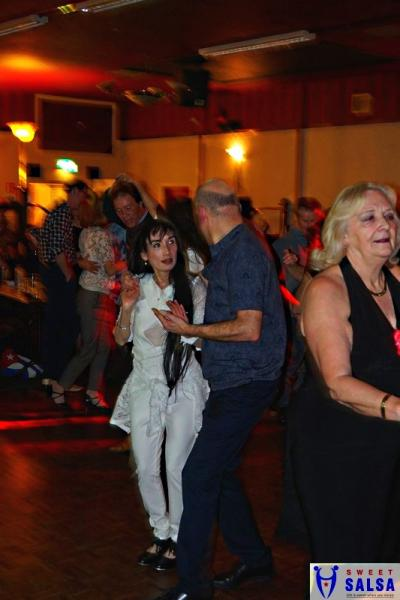 2 people dancing. lady dressed in white