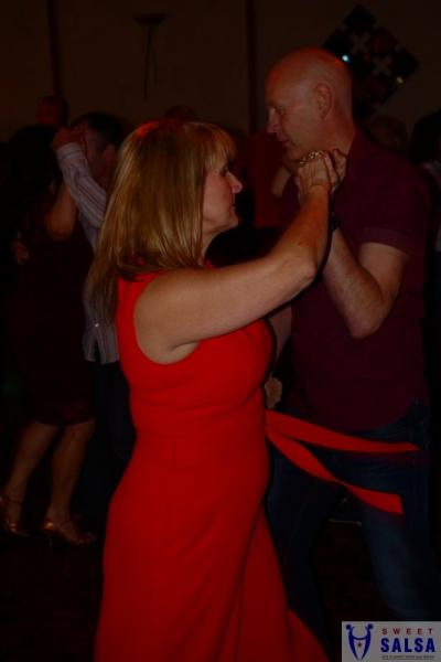 2 people dancing to salsa music. One in a red dress