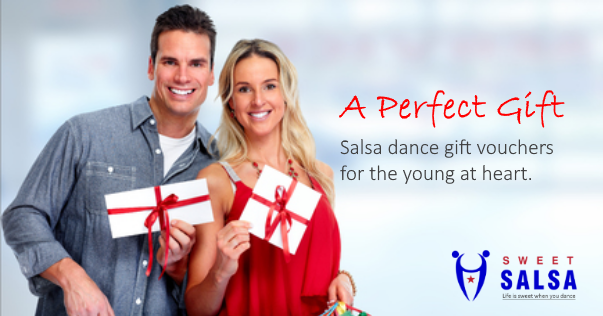 young couple holding salsa gift vouchers